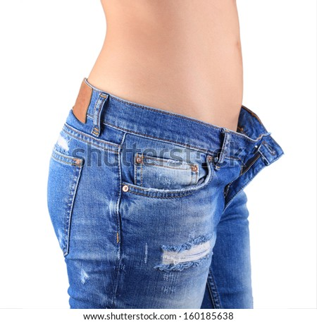 Woman waist wearing jeans. Weight loss stomach closeup. Skinny jeans on a healthy slim fit body.  - stock photo