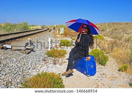Woman waiting for the train in the sun