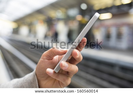 Woman waiting on subway platform with her cell phone  - stock photo