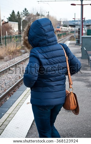 woman waiting the train with  goose feathers jacket in train station