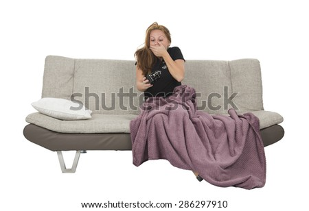 Woman waking up after having a nap on a sofa against a white background - stock photo
