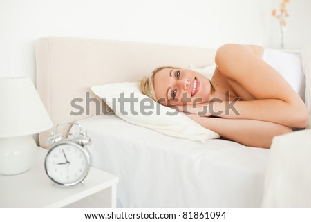 Woman waking up and an alarm clock in her bedroom - stock photo