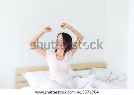 Woman waking up and yawning with a stretch - stock photo