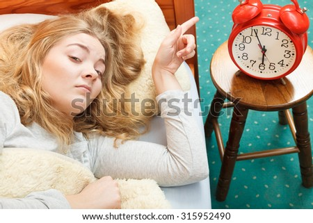 Woman waking up in bed turning off alarm clock. Young girl in the morning.