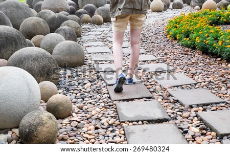 woman walk alone on way brick in public garden - stock photo