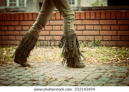 woman walk in dark green tassel boots in front small brick wall on cobble path, day shot - stock photo