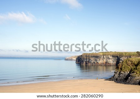 woman walking a dog as soft waves break on the beach cliffs at ballybunion