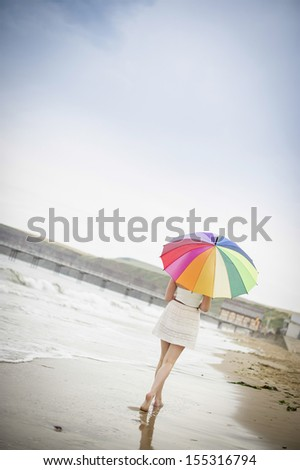 Woman walking alone along the beach as the tide comes in with a large multi-coloured umbrella