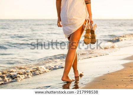 Woman walking alone on the beach - stock photo