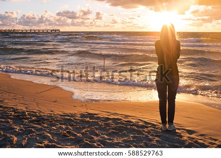Woman walking alone on the beach in the sunset