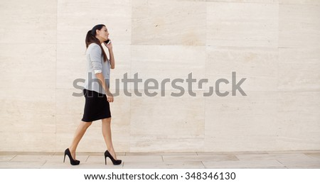 Woman walking along a sidewalk past a neutral cream colored wall with copyspace chatting on her mobile phone