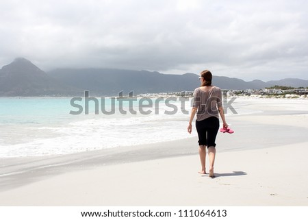 Woman walking along the Beach of Kommetjie with an upcoming storm in the background