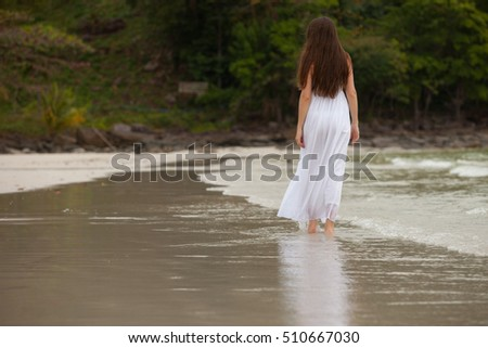 woman walking among shoreline
