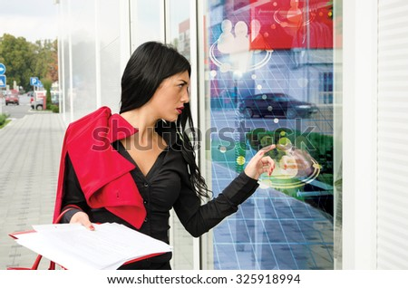 woman walking and touching screen outside - stock photo