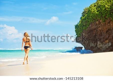 woman walking away on the idylic beach - stock photo