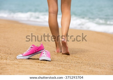 Woman walking barefoot on sandy coast, shoes in focus, shallow DOF