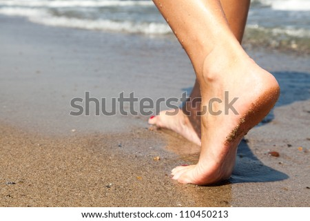 Woman walking barefoot on sunny beach in summer day