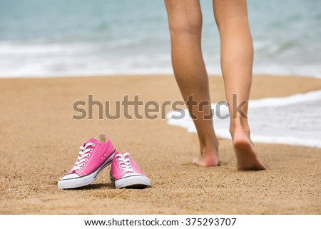 Woman walking barefoot on the beach, shoes in focus, shallow DOF