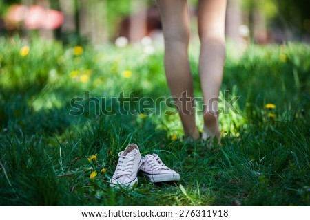 Woman walking barefoot on the grass, pink shoes in focus, shallow DOF - stock photo