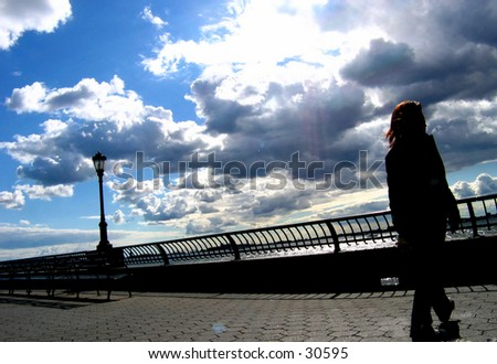 Woman walking by Battery Park. Developing Thunder Clouds - stock photo