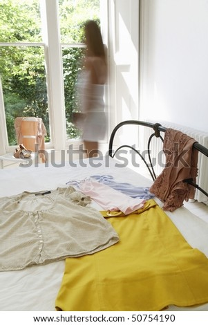 Woman walking by outfit laid out on bed - stock photo