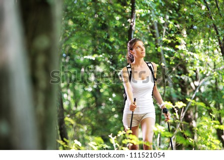 Woman walking cross country in a green forest - stock photo