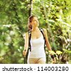 Woman walking cross country in forest - stock photo