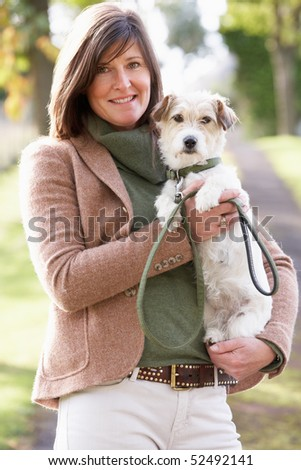Woman Walking Dog Outdoors In Autumn Park - stock photo