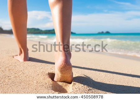 Woman walking down a beautiful tropical beach.