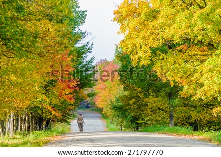 Woman walking down a country road in the fall, Stowe, Vermont, USA - stock photo