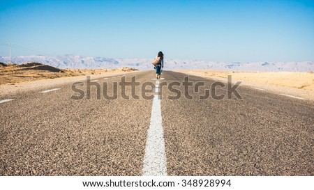 Woman walking down middle of highway with a few belongings. - stock photo
