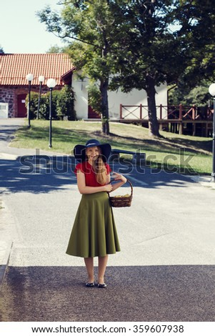Woman walking down the street with basket - stock photo