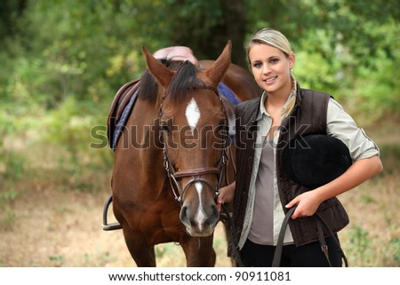 Woman walking horse - stock photo