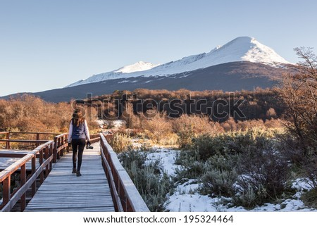 Woman walking in a balcony with a beautiful landscape in the background. Ushuaia, Argentina - stock photo
