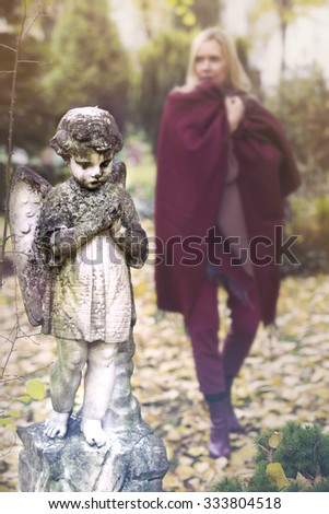 woman walking in cemetery next to statue of little angel - stock photo