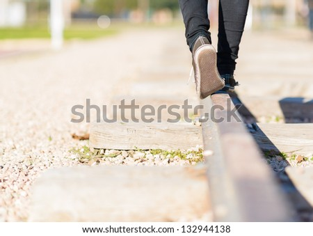 Woman Walking In Equilibrium Over Railroad - stock photo