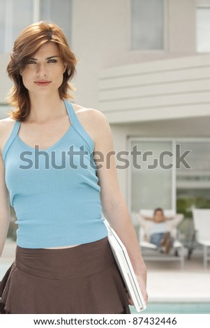 Woman walking in home garden, holding a laptop.