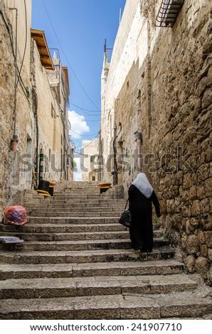 Woman walking in Jerusalem old city - stock photo