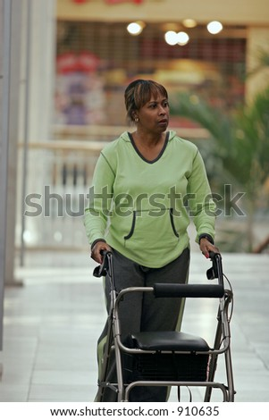 woman walking in mall using walker - stock photo