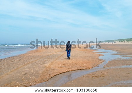 Woman walking on a beach in spring