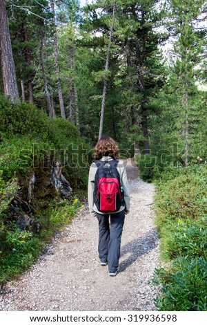woman walking on a path in the woods with a backpack - stock photo