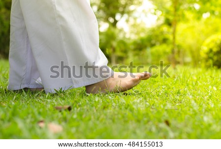 Woman walking on green grass for relaxation and meditation