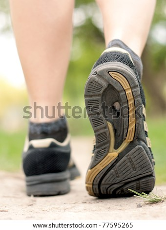 Woman walking on hiking trail in forest, sport shoe closeup