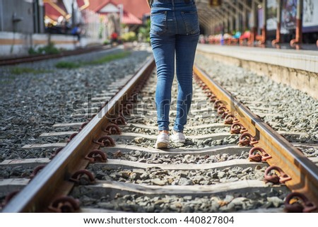 Woman walking on railway tracks - stock photo
