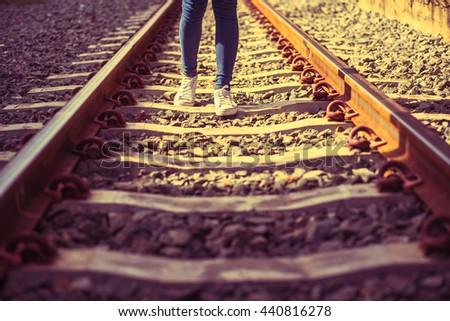 Woman walking on railway tracks.vintage tone. - stock photo