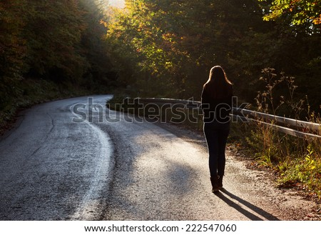 Woman walking on road in autumn afternoon. Beautiful autumn scene. - stock photo