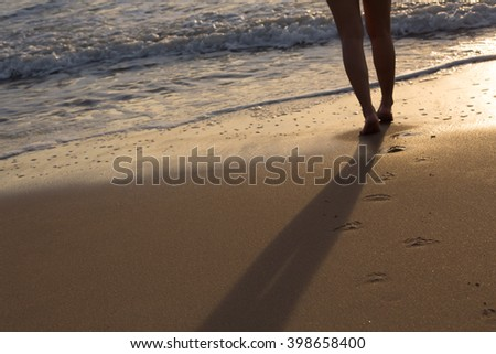 woman walking on sand beach in the morning