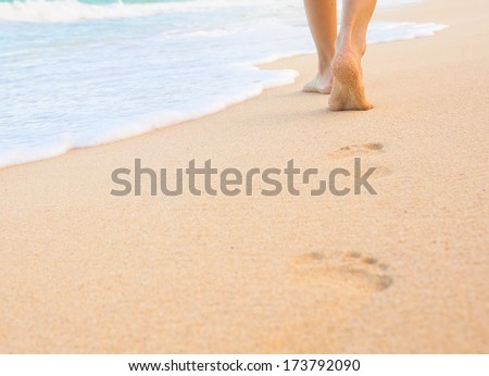 Woman walking on sand beach leaving footprint in the sand. Beach travel. - stock photo