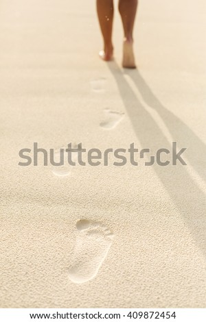 Woman walking on sand beach leaving footprints in the sand. Beach travel concept. - stock photo