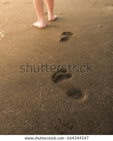 Woman walking on sand beach leaving footprints in the sand. Close Up detail. golden sand on beach in Bali.